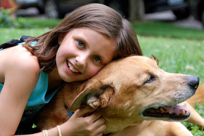 girl cuddling dog
